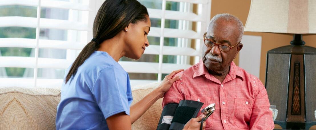 caregiver checking blood pressure to the senior man