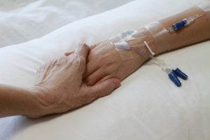 hand holding patient with IV drip