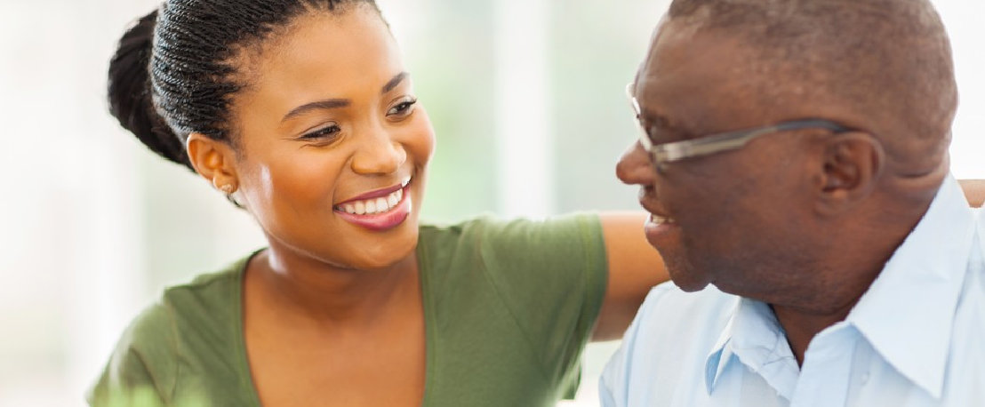 caregiver and senior man smiling each other