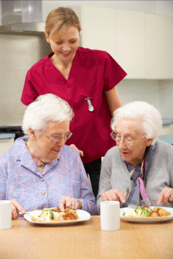 caregiver giving meals to patients